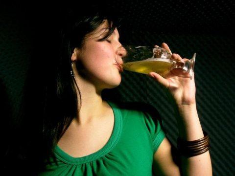 Девушка пьет пиво из бокала